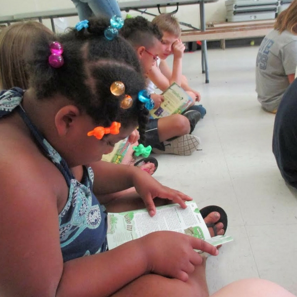 Reading with kids helps them improve their literacy skills.